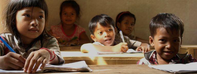 Nens a l'escola, aprenent a llegir i escriure