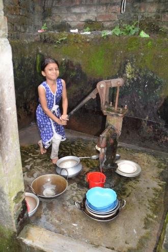 Niña sacando agua de un pozo en Chattogram, Bangladesh. Foto: Manos Unidas/Patricia Garrido