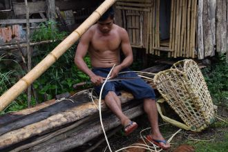 Un pescador de Filipinas elaborando una cesta de pesca.
