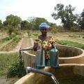 Una de las mujeres beneficiarias de esta iniciativa junto al pozo que riega sus huertos. Foto: Manos Unidas