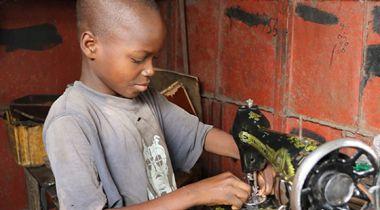 Un niño arregla una máquina de coser en el mercado Dantopka en Cotonou, Benín. Foto Iciar de la Peña-Manos Unidas